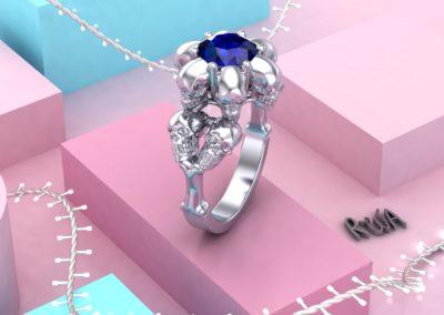 Anello di fidanzamento con zaffiro blu e teschi. / Engagement ring with blue sapphire and skulls.